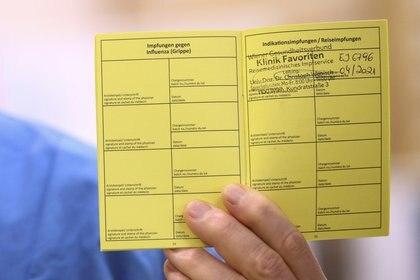 Un trabajador de la salud muestra una tarjeta de vacunación COVID-19 de Pfizer-BioNTech en el Hospital Favoriten de Viena, Austria