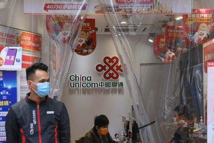 Sales assistants work at a China Unicom Hong Kong Ltd. store in Hong Kong. Photographer: Roy Liu/Bloomberg