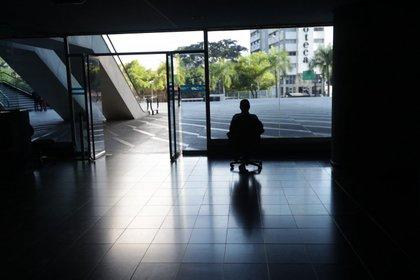 Un hombre mira por la ventana en una oficina sin luz en Caracas (EFE/ Rayner Peña)