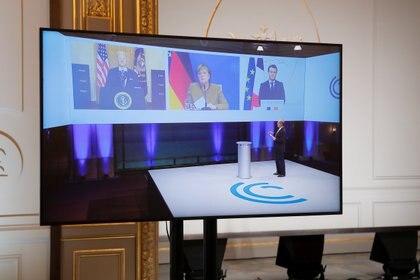 Fotografía que muestra la videollamada del presidente francés, Emmanuel Macron, el presidente de Estados Unidos, Joe Biden, y la canciller alemana, Angela Merkel, por la Conferencia de Seguridad de Múnich 2021 (REUTERS/Benoit Tessier)