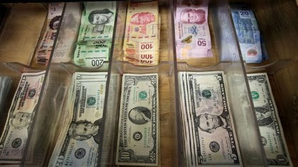 FOTO DE ARCHIVO. Billetes de peso mexicano y dólar estadounidense aparecen en una tienda de cambio de divisas en Ciudad Juárez, México. 15 de enero de 2018. REUTERS/José Luis González.