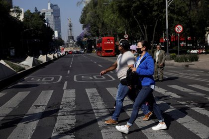 Personas cruzan avenida Reforma casi vacía en Ciudad de México. 20 de marzo de 2020. REUTERS/Luis Cortes
