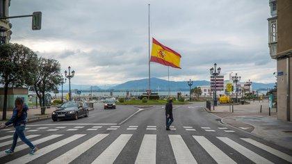 Varios peatones cruzan una calle delante de una bandera que ondea a media asta en memoria de las víctimas de coronavirus en Santander. EFE/Román G. Aguilera/Archivo