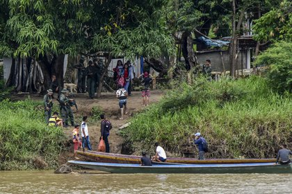 Venezolanos desplazados se suban a botes para cruzar el río La Victoria (Daniel MARTINEZ / AFP)