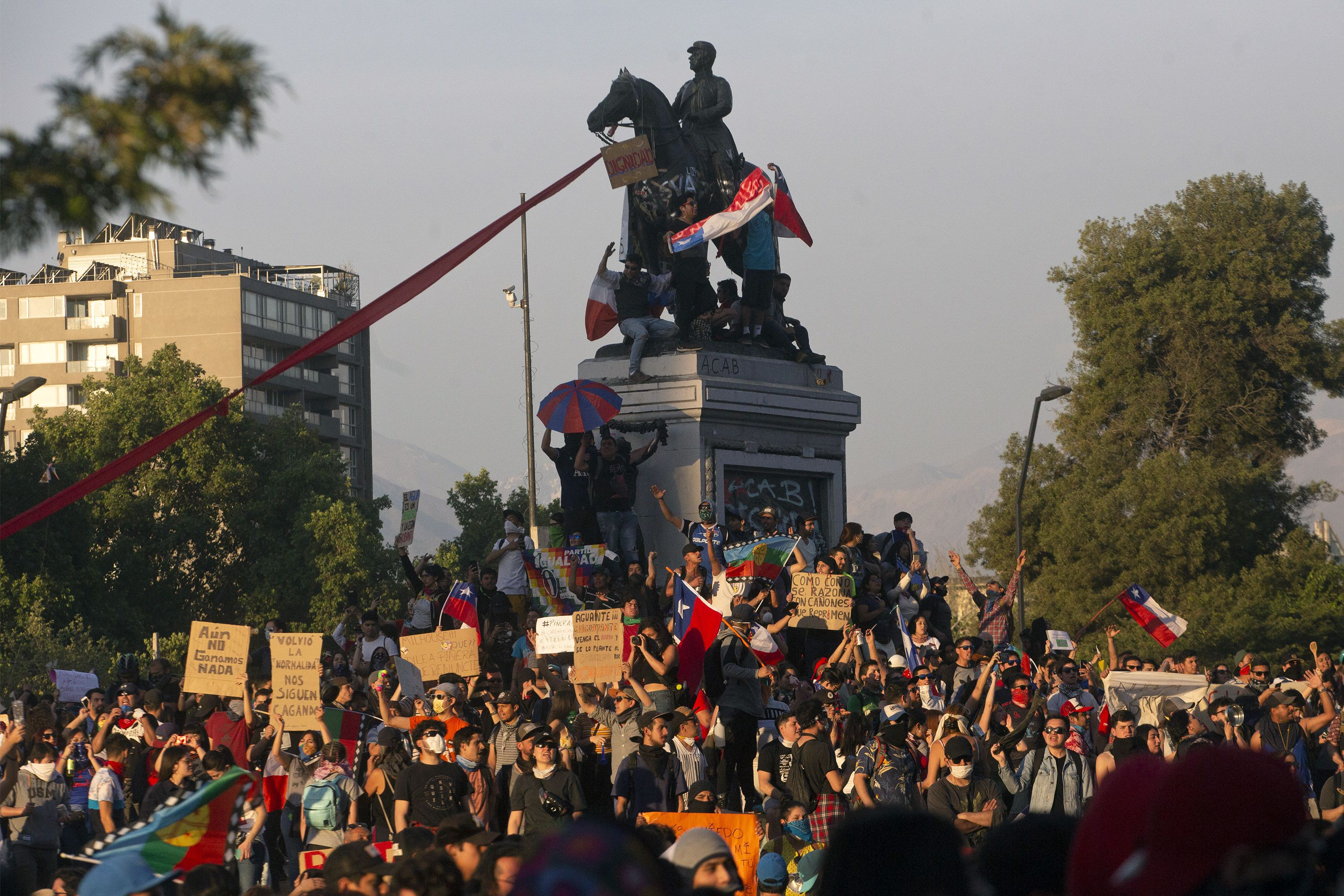 People demonstrate against the government economic policies in Santiago, on October 26, 2019, a day after more than one million people took to the streets for the largest protests in a week of demonstrations. - Chilean President Sebastian Pinera on Saturday announced a major government reshuffle and the military lifted the nighttime curfew in the Chilean capital Santiago, after a week of deadly demonstrations demanding economic reforms and Pinera's resignation. (Photo by CLAUDIO REYES / AFP)