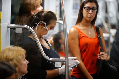 Una mujer con barbijo y guantes usa su smartphone en el subte de  Buenos Aires (REUTERS/Agustin Marcarian)