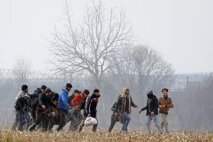 Los migrantes llevan a un hombre herido cerca del cruce fronterizo Pazarkule de Turquía con Kastanies de Grecia, cerca de Edirne, Turquía (REUTERS / Huseyin Aldemir)