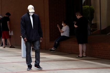 Un hombre que perdió su trabajo pasa por delante de otros mientras esperan en fila para solicitar el seguro de desempleo en Fort Smith, Arkansas, el 6 de abril de 2020 (REUTERS/Nick Oxford)