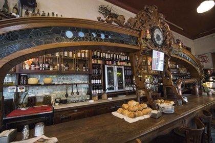 La famosa barra. Con reloj de agujas y una llamativa estructura de madera y vidrio de color,allí los clientes habitúes del lugar toman asiento para disfrutar de los tradicionales platos de la casa