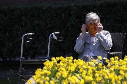 """Una residente del hogar """"De Ravenstein"""" se acomoda un pañuelo que hace las veces de máscara protectora en Boortmeerbeek, Bélgica April 7, 2020.  REUTERS/Yves Herman"""
