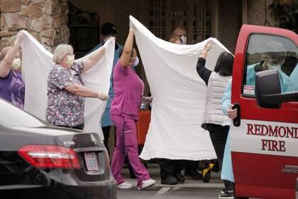 Médicos y otros trabajadores de la sanidad trasladan a un paciente en camilla a una ambulancia en el centro LifeCare de Kirkland, el centro de cuidados a largo plazo relacionado con dos de los tres casos de coronavirus confirmados en el estado, en Kirkland, Washington, EEUU 1 de marzo , 2020. REUTERS/David Ryder