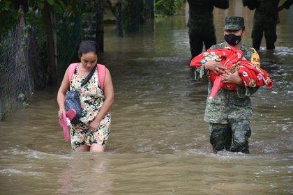 Un miembro del Ejercito mexicano mientras presta auxilio a una mujer y su hijo, durante las inundaciones en Nacajuca, en el estado de Tabasco (Foto: EFE/Presidencia)