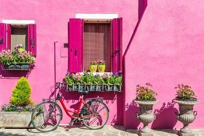 La ciudad de Burano se caracteriza por tener pequeñas casas con sus fachadas de colores estridentes y llamativos. Muchos eligen el magenta para que resalte el color cuando el sol alumbra las paredes (Getty)