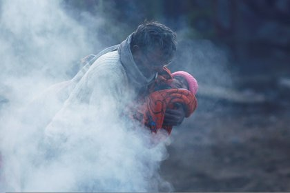 A man holding a baby wrapped in a blanket stands next to a bonfire on a cold winter morning in New Delhi, India, December 19, 2018. REUTERS/Adnan Abidi     TPX IMAGES OF THE DAY