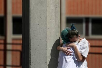 Dos trabajadoras sanitarias se abrazan afuera de las salas de emergencia del hospital Severo Ochoa en Leganes (REUTERS/Susana Vera)