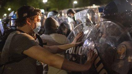 Manifestante forcejea contra un policía afuera de la Casa Blanca durante las protestas de la madrugada por la muerte de George Floyd (Foro: Eric BARADAT / AFP)