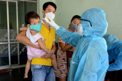 A health worker gets the temperature of residents at the area of a newly found coronavirus infected patient in Da Nang city, Vietnam July 26, 2020. Quoc Dung/VNA via REUTERS.