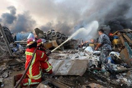 Bomberos trabajan para apagar el incendio provocado por las explosiones. REUTERS/Mohamed Azakir