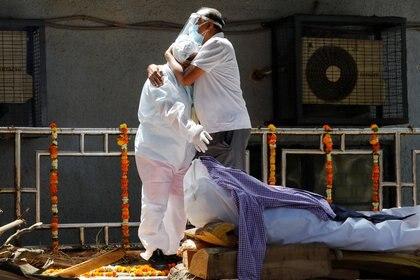 Personas con equipo de protección personal lloran por la muerte por covid de un familiar en un crematorio en Nueva Delhi. REUTERS/Adnan Abidi