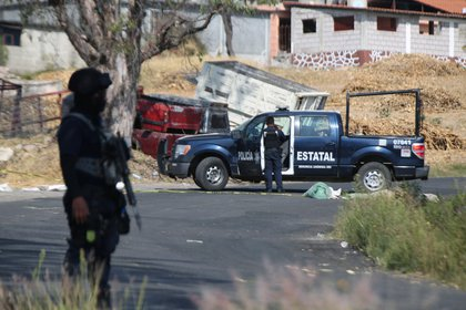 Police officers work at a crime scene where gunmen killed at least 13 Mexican police officers in an ambush, in Coatepec Harinas, Mexico March 19, 2021. REUTERS/Edgard Garrido