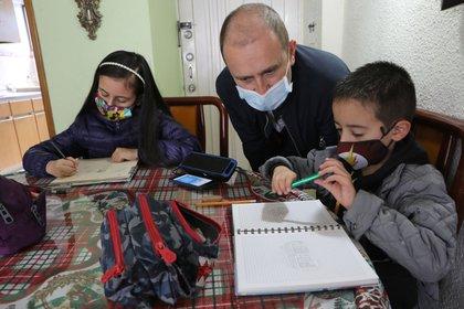 Diego Mora (c) acompaña a sus hijos Isabela (i) y Juan Diego mientras dibujan y escuchan el programa de radio Aprende en Casa de la Secretaría de Educación durante el confinamiento obligado por la pandemia del COVID-19, el 5 de junio de 2020, desde su apartamento en Bogotá (Colombia).EFE/Carlos Ortega