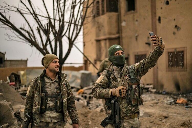 """Tropas kurdas se toman una selfie tras la caída de Al Baguz, último bastión del """"califato""""(Delil souleiman / AFP)"""