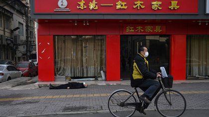 Un hombre circula tranquilamente en su bicicleta mientras un cadáver yace en la vereda contigua, aún con la mascarilla para reducir las chances de contagio sobre su rostro (AFP / Héctor RETAMAL)