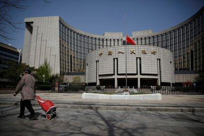 La bandera nacional china ondea a media asta en la sede del Banco Popular de China, el banco central (PBOC), en Pekín, China, el 4 de abril de 2020.  REUTERS/Carlos Garcia Rawlins