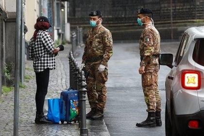 Soldados italianos con máscaras protectoras piden a los peatones sus documentos, después de que Italia reforzara las medidas de bloqueo para combatir el COVID-19 en Catania, Italia, el 21 de marzo de 2020. (REUTERS/Antonio Parrinello)