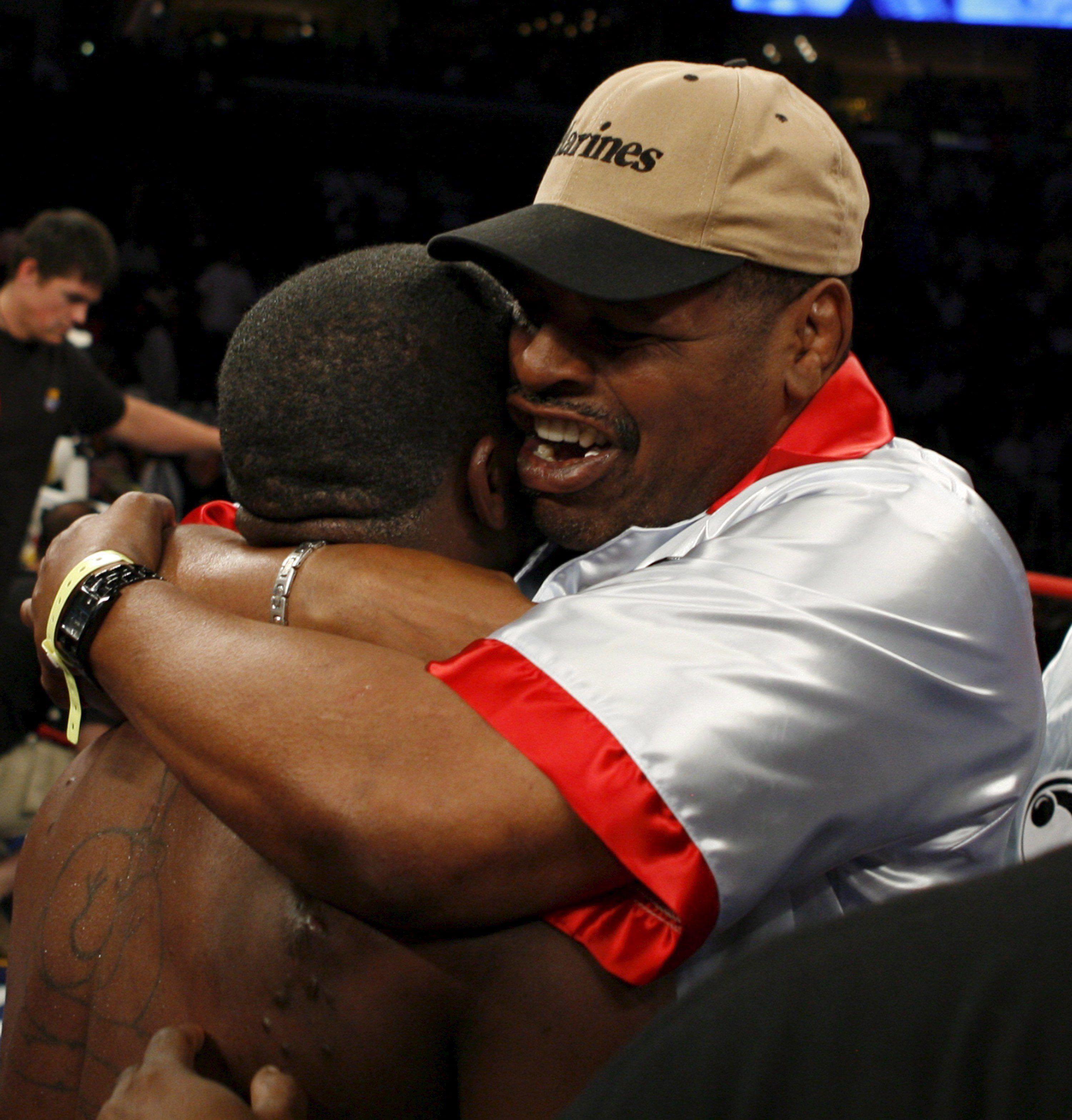 El boxeador Cory Spinks (i) recibe un abrazo de su padre, el ex campeón de medio peso Leon Spinks tras perder una pelea. EFE/MIKE BROWN/Archivo