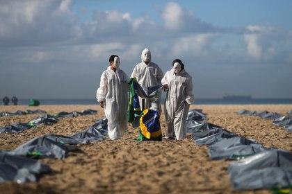 Activistas de la ONG Río de Paz llevan una bandera brasileña mientras muestran cientos de bolsas de plástico, que representan cadáveres, durante una protesta contra las políticas de Jair Bolsonaro, en medio del brote de la enfermedad del coronavirus (COVID-19), en la playa de Copacabana, en Río de Janeiro, Brasil,