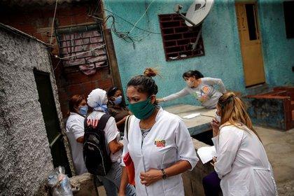 Un equipo formado por trabajadores de la salud cubanos y venezolanos participa en una ronda de inspección en el barrio marginal de Lídice, durante la cuarentena a nivel nacional debido al brote de la enfermedad por coronavirus (COVID-19), en Caracas, Venezuela. 9 de abril de 2020. REUTERS/Manaure Quintero.