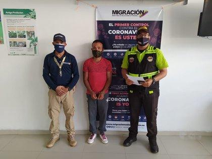 Fotografía cedida hoy por Migración Colombia que muestra a agentes que custodian al ciudadano venezolano Alberto José Ramos (c), en Maicao (Colombia). EFE/ Migración Colombia