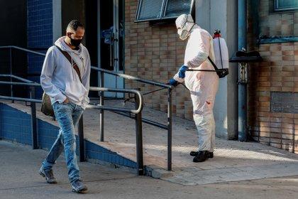 Un agente municipal desinfecta la fachada de una unidad de salud en Sao Paulo. (Foto: Sebastião Moreira/EFE)