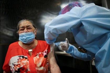 Foto de archivo. Una mujer recibe su primera dosis de la vacuna china Sinovac Biotech para la enfermedad del coronavirus (COVID-19) durante un programa de vacunación masiva para ancianos en el Movistar Arena en Bogotá, Colombia. 9 de marzo, 2021. REUTERS/Luisa González