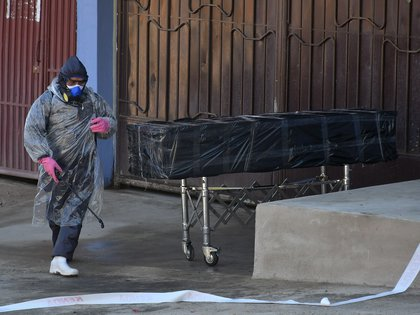 Empleados de una funeraria retiran el cuerpo sin vida de un hombre que permaneció durante horas abandonado en una calle, este domingo en Cochabamba (Bolivia). EFE/Jorge Ábrego
