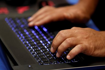 FILE PHOTO: A man types into a keyboard during the Def Con hacker convention in Las Vegas, Nevada, U.S. on July 29, 2017. REUTERS/Steve Marcus/File Photo
