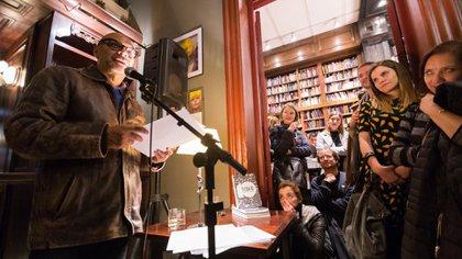 Fabián Casas lee en la noche de poesía del Filba; Martín Kohan, de rodillas, entre el público (Rodrigo Ruiz)
