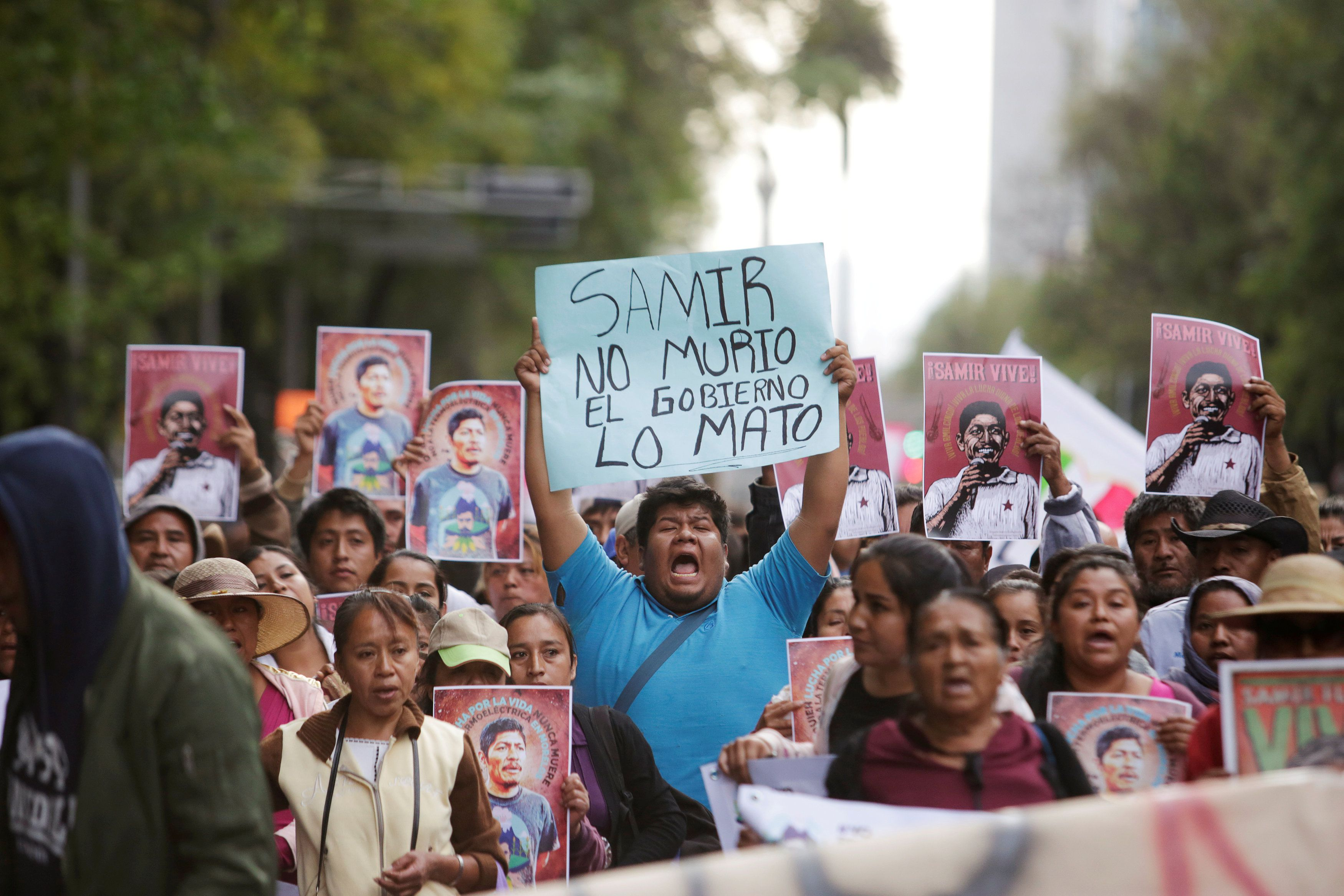 A man holds up a placard reading 'Samir didn't die, the government killed him' during a protest to demand justice for Mexican activist Samir Flores Soberanes, who opposed to a thermoelectric project promoted by the government of President Andres Manuel Lopez Obrador, and was later gunned down by unknown assailants, in Mexico City, Mexico February 22, 2019. REUTERS/Daniel Becerril     TPX IMAGES OF THE DAY