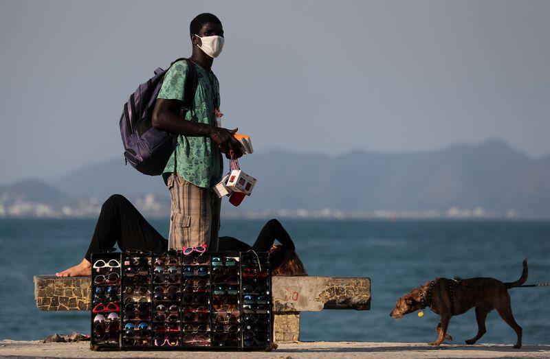Un hombre vende lentes de sol en la playa de Copacabana en Río de Janeiro. FOTO DE ARCHIVO. Julio, 2020 REUTERS/Sergio Moraes