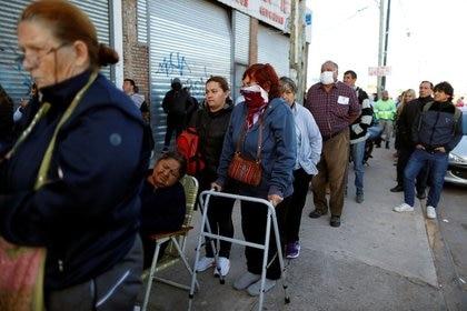 A comienzos de abril, jubilados y personas con planes de asistencia social hacen cola fuera de un banco (REUTERS)