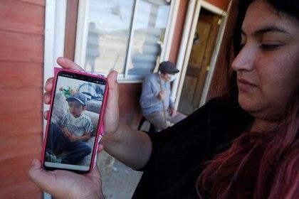 Una mujer muestra una foto del niño Tomás Bravo, de tres años, que desapareció el 17 de febrero cuando salió con un tío en busca de animales.  Tras nueve días, el cuerpo sin vida del menor fue hallado a dos kilómetros de donde se vio por última vez.