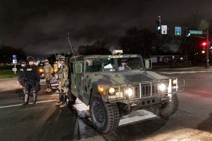 Agentes de policía, soldados de la Guardia Nacional y vehículos bloquean la carretera cerca de la estación de policía de Brooklyn Center mientras la gente se reúne para protestar después de que un oficial de policía disparó y mató a un hombre negro en Brooklyn Center, Minneapolis, Minnesota el 12 de abril de 2021. (Photo by Kerem Yucel / AFP)