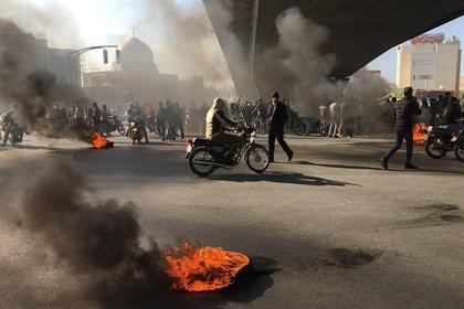 Manifestantes iraníes durante una protesta contra el alza de los combustibles (Photo by - / AFP)