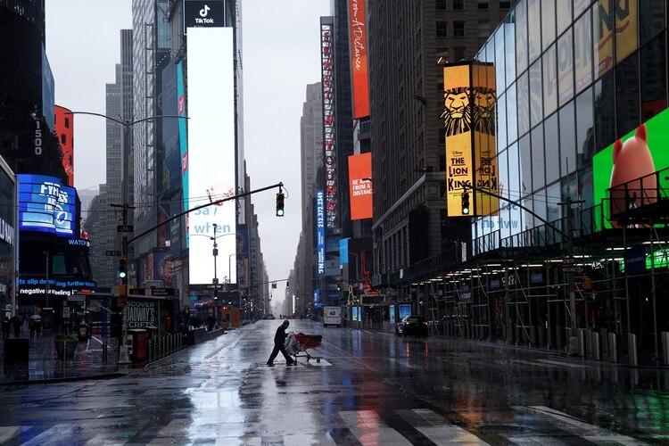 Una persona sin hogar empuja sus pertenencias a través de un Times Square desierto después del brote de la enfermedad por coronavirus (COVID-19). La economía norteamericana está virtualmente detenida y las alarmas sobre las consecuencias comienzan a sonar (Reuters)