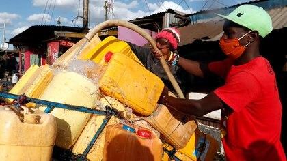Un vendedor llena bidones de agua para su venta, en medio de la escasez de agua durante la propagación del brote de coronavirus en Nairobi, Kenia, el 13 de mayo de 2020 (REUTERS/Njeri Mwangi)