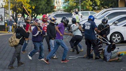 Varios miembros de las fuerzas antichoque del gobierno agreden a una persona.