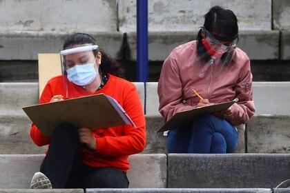 Jóvenes completan formularios durante la pandemia de Covid-19. Foto: REUTERS/Edgard Garrido