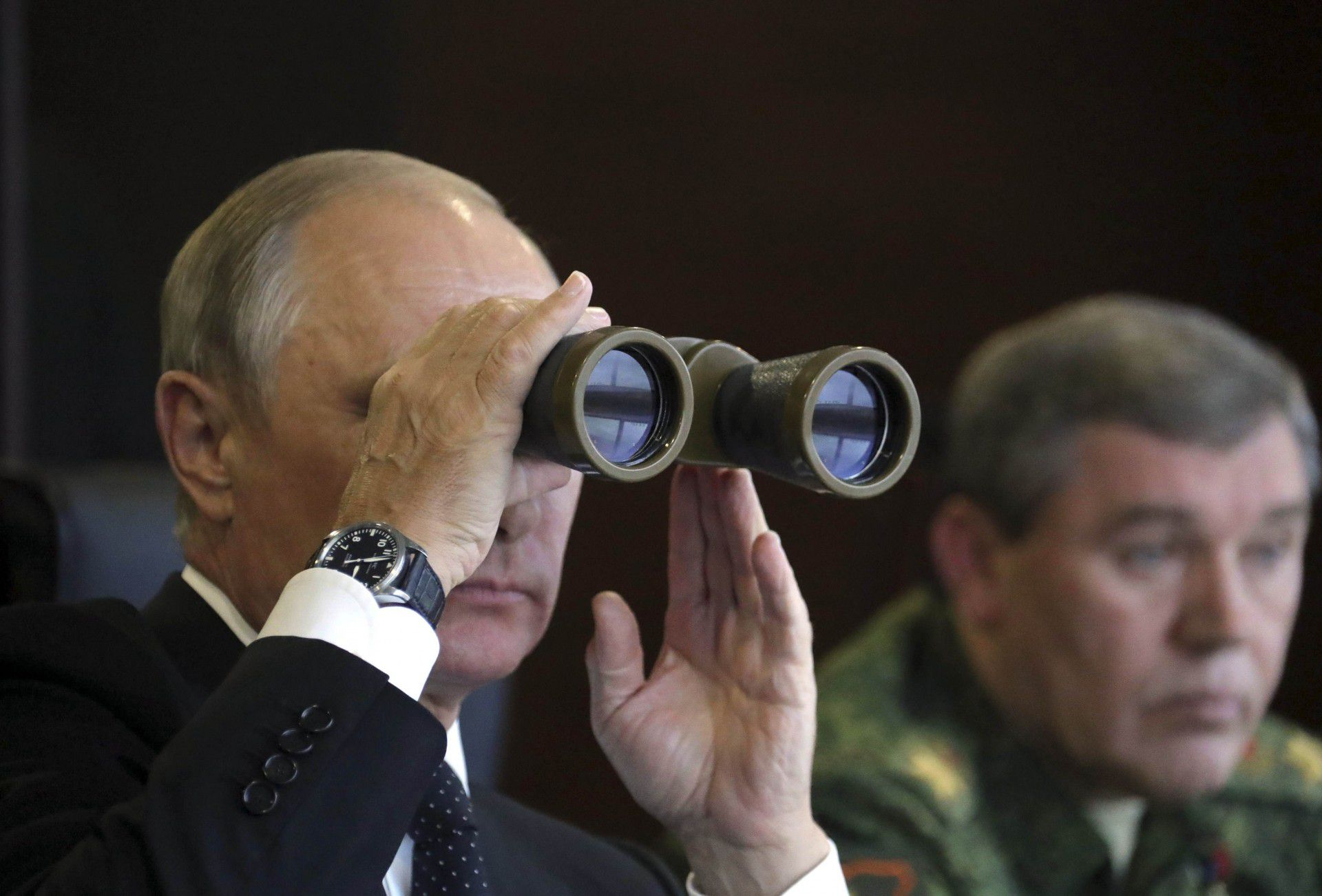 Russian President Vladimir Putin uses a pair of binoculars while watching the Zapad-2017 war games, held by Russian and Belarussian servicemen, with Chief of the General Staff of Russian Armed Forces Valery Gerasimov seen nearby, at a military training ground in the Leningrad region, Russia September 18, 2017. Sputnik/Mikhail Klimentyev/Kremlin via REUTERS ATTENTION EDITORS - THIS IMAGE WAS PROVIDED BY A THIRD PARTY.