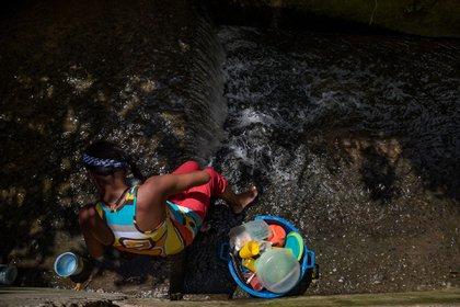 Una mujer lavando utensilios de cocina en una quebrada de agua, en Caracas (EFE/ Miguel Gutiérrez)